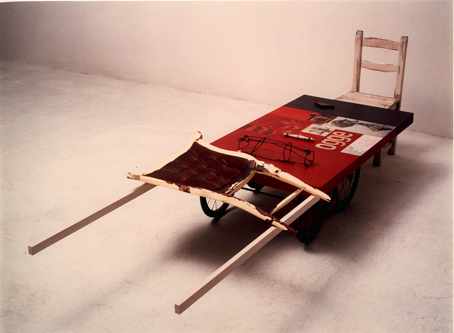 Carro para Sísifo. 2000. Assemblage: Acrílico/fotografía y madera, objetos, estructura metálica y respoaldo de silla/estructura de madera con ruedas y silla. 75 x 284 x 85 cm.